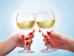Two female hands toasting with white wine on blue background, close up