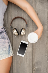 On the floor / Beautiful young woman lying on the wooden floor with music headphones, smartphone and a take away coffee cup; view from above.