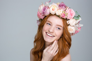 Charming cheerful woman with red hair in beautiful flower wreath