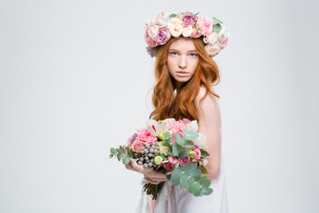 Beautiful female in wreath of roses posing with flower bouquet