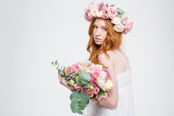 Fashion portrait of beautiful woman in wreath holding flowers bouquet