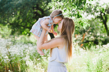 Young mother playing with her little daughter on the nature, motherhood, tenderness, childhood, tenderness, lifestyle
