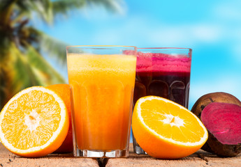 Fresh juices, orange, beetroot and carrot on wooden table with tropical beach background
