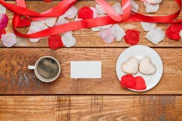 The red  ribbon on  wooden background with a cup of coffee
