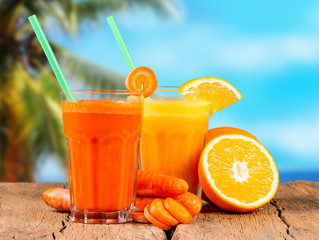 Fresh juices, orange and carrot on wooden table with tropical beach background