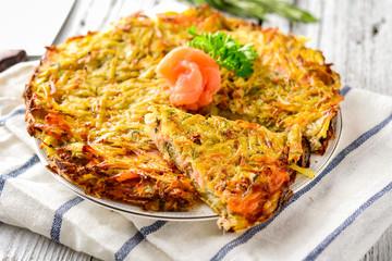 Potato pie (big potato latkes) with salmon garnished with parsley