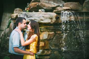 beautiful couple in love in the arms of waterfall
