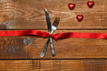 The red ribbon, fork and knife on wooden background