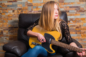 Attractive young girl in blue jeans and black lace shirt sitting in chair and playing guitar on brick background