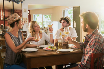 In a warm house, two couples of friends having fun during a lunch