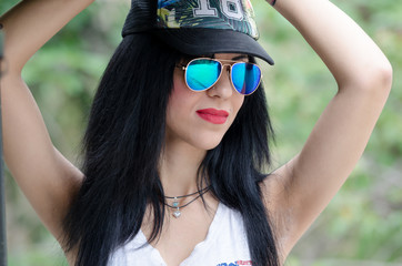 Woman with r&b style wearing colored mirror sunglasses shirt and hat, hands over head looking away