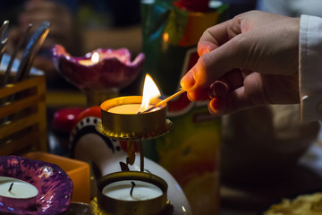 background blurred woman's hand lights a candle in a candlestick with a match at dusk