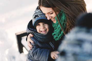 Cute young pregnant mother and her child having fun in winter park on a bright day hugging each other and smiling