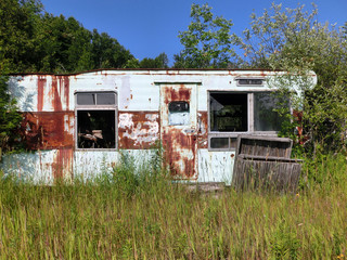 Abandoned rusted motor home in overgrown grass