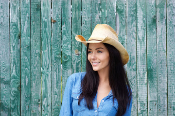 Attractive young brunette woman smiling with cowboy hat