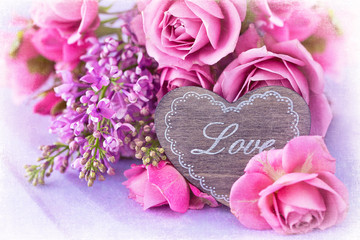 Lilacs and pink roses flowers decorated with a wooden heart. .Floral gift for a wedding or birthday.