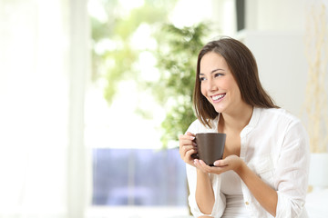 Woman drinking coffee or tea at home