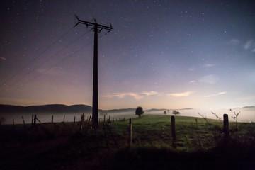 photo de nuit dans la campagne sous le ciel étoilé de l'été, un poteau électrique et un pré