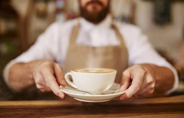 Fototapeta Barista serving cup of fresh coffee for you obraz
