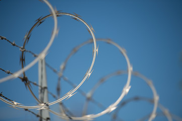concertina and barbed wire fence against a blue sky