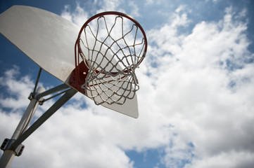 basket ball hoop outside against a blue sky with clouds