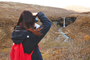 Back view of young woman taking pictures of Svartifoss waterfall
