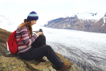 Young woman with backpack sitting near glacier in Iceland. Backp