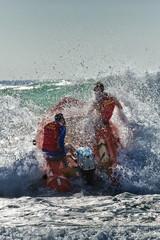 Surf lifesavers power their dinghy through powerful waves