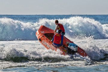 Surf lifesavers guide their dinghy out from the beach into heavy surf.