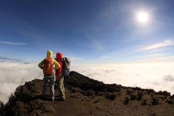 two successful backpacker enjoy the beautiful landscape at sunrise mountain peak