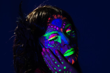 Headshot woman wearing awesome glow in dark facial paint, blue based with other neon colors and obscure abstract background, facing camera