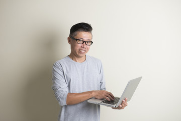 asian casual senior with laptop