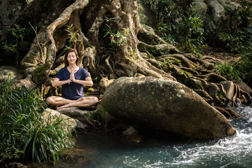 Woman meditate under banyan tree near river in the jungle. Yoga lifestyle concept