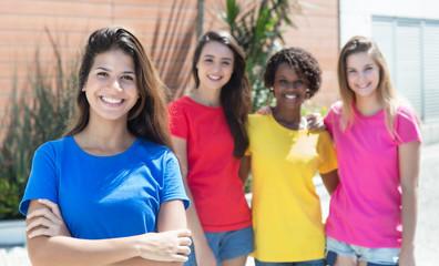 Lachende junge Frau im blauen Shirt mit Freundinnen