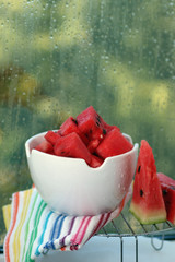 slices of watermelon in a bowl on a blurred background