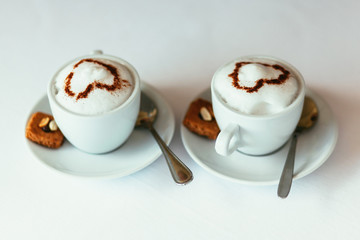 Two cups of gourmet coffee house cappuccino with cookies against