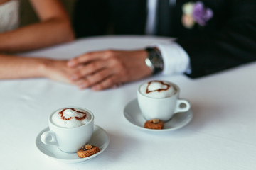 bride's and groom's hands holding each other on a table with two