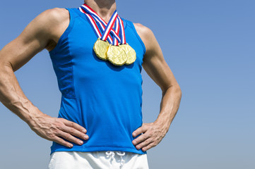 Athlete standing with three gold medals hanging from a red white and blue ribbons against blue sky