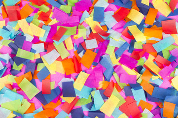Brightly colored paper confetti background featuring red, yellow, blue, green, orange, and bright pink carnival colors