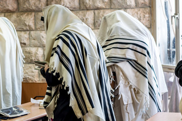 Jewish men praying in a synagogue with tallit