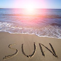 Sun written on wet sand