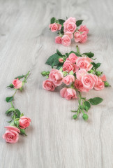 Small pink roses on wooden table,