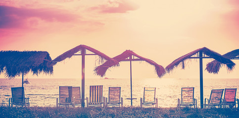 Vintage toned beach chairs and umbrellas at sunset, holidays bac