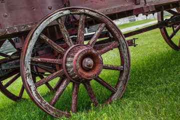 Pioneer Transportation. Wooden wheel on a weathered and worn covered wagon.