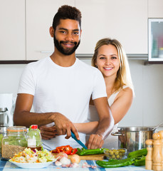 Interracial couple preparing healthy dinner.