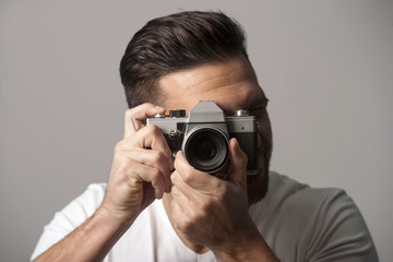 Handsome man holding manual film camera taking picture