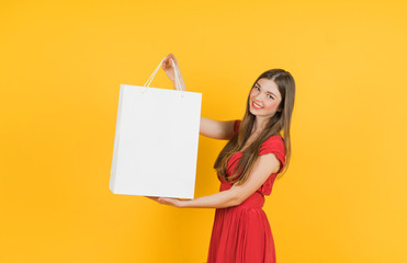 Smiling beautiful woman with shopping bag on yellow background