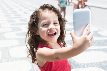 Kleines Kind im roten Shirt macht Foto mit Handy