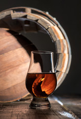 A glass of whiskey on the oak barrel