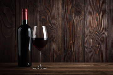 Red wine bottle and glass of wine on the dark wooden background